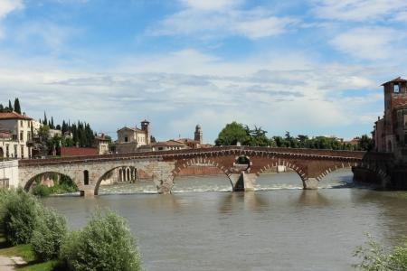 The Italian city of Verona. A kind on bridge Ponte Pietra and river Adige  Фото со стока