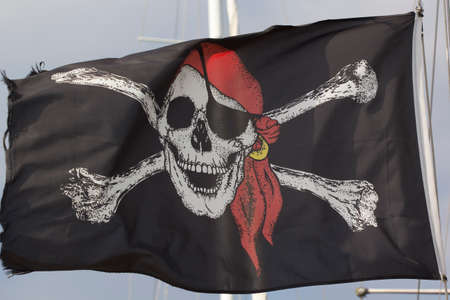 roger: Jolly Roger Black Pirate Flag With Human Skull On Blue Sky Stock Photo