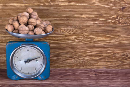 calibrate: Mechanical Scales with Walnuts on the wooden background Stock Photo