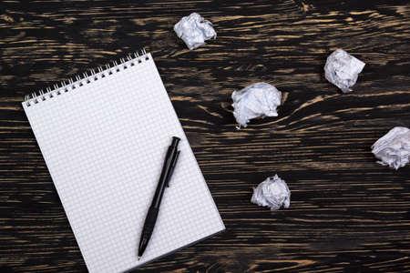 nota de papel: bolas de papel arrugado con gafas y portátil en el escritorio de madera Foto de archivo