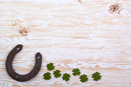 Fabric green clover leaves with horseshoe on light wooden background.