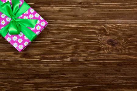 felicitaciones cumpleaÑos: Caja de regalo con la cinta en la mesa de madera de color marrón