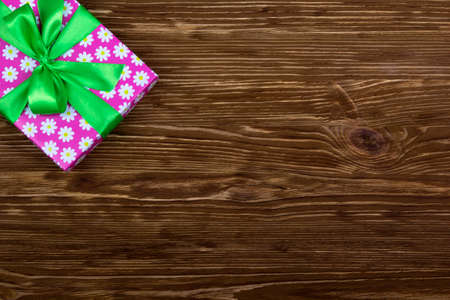 gift parcel: Gift box with ribbon on brown wooden table Stock Photo
