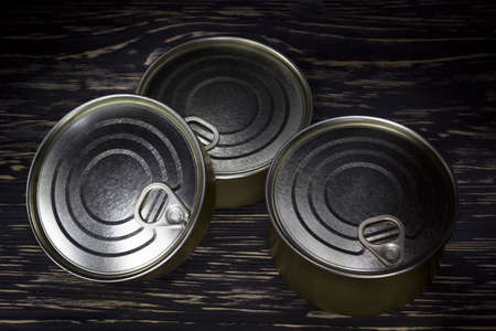 tinned goods: Three conserve can on dark wooden background
