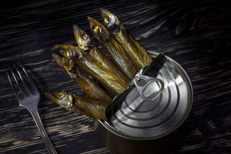 tinned: Close-up of Tinned capelin fish on dark wooden background