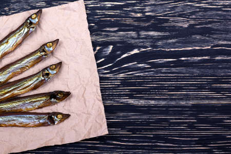 Smoked  capelin on dark vintage wooden background, top view