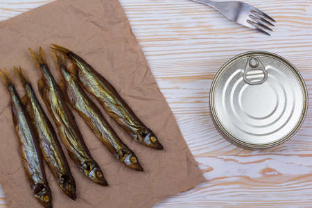 tinned goods: Smoked capelin and conserve tins on light wooden background