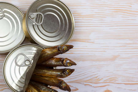 tinned: Close-up of Tinned capelin fish on light wooden background
