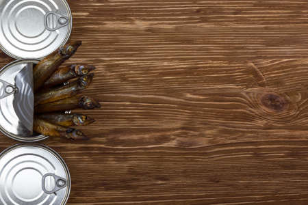tinned: Close-up of Tinned capelin fish on brown wooden background