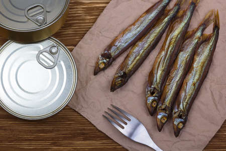 tinned goods: Smoked capelin and conserve tins on brown wooden background Stock Photo