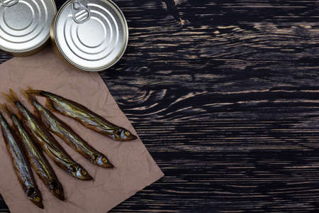 conserve: Smoked capelin and conserve tins on dark wooden background