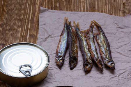 tins: Smoked capelin and conserve tins on brown  wooden background