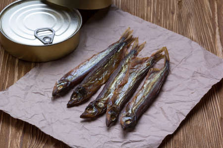 conserve: Smoked capelin and conserve tins on brown  wooden background