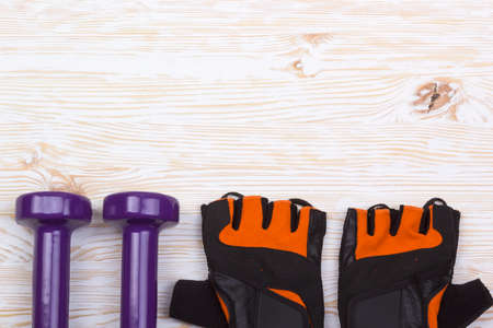weightlifting gloves: dumbbell and fitness gloves on light wooden background