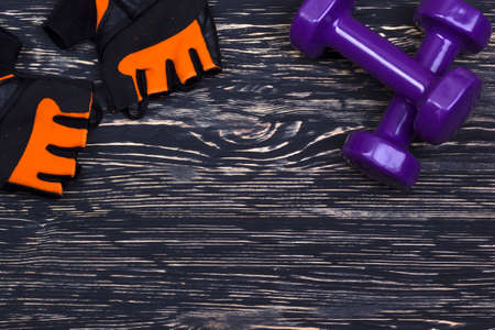 weightlifting gloves: dumbbell and fitness gloves on dark wooden background Stock Photo