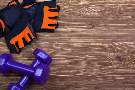 weightlifting gloves: dumbbell and fitness gloves on brown wooden background