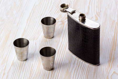 Metal flask trimmed leather and three metallic, sturdy shot glasses on a wooden background Stock Photo