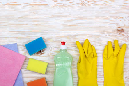 sanitizing: Detergent,sponges, rags and latex gloves on wooden background