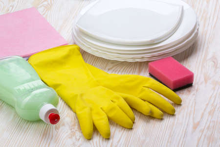 latex gloves: Detergent,sponge, dishes, rag and latex gloves on wooden background Stock Photo