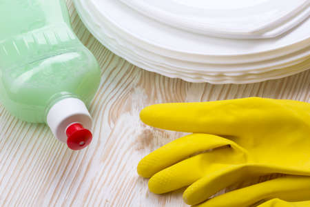 latex gloves: Detergent, dishes and latex gloves on wooden background Stock Photo