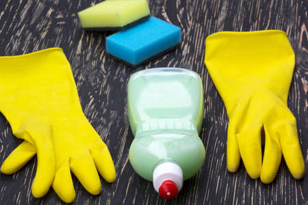 latex gloves: Detergent,sponges  and latex gloves on wooden background