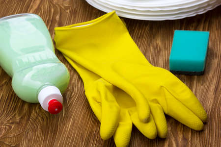 sanitizing: Detergent,sponge, dishes and latex gloves on wooden background
