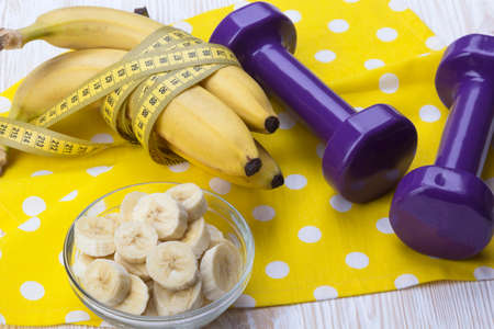 measurement tape: bunch of bananas, measurement tape and dumbbells on wooden table