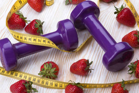 summer sport: Strawberries, measurement tape and dumbbells on wooden table