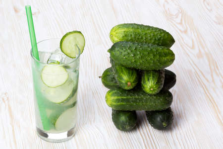 shooter drink: Summer cucumber cocktail and cucumbers on wooden desk.