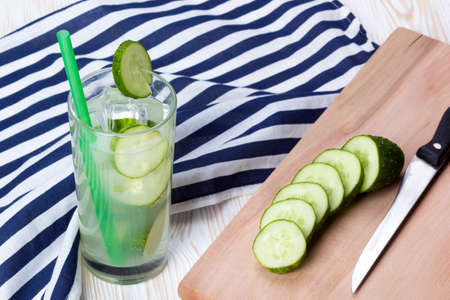 shooter drink: Summer cucumber cocktail, knife and sliced cucumbers on wooden desk. Stock Photo