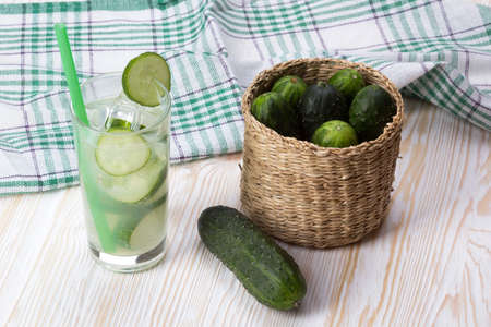 shooter drink: Summer cucumber cocktail and cucumbers in the basket on wooden desk.
