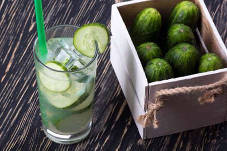 shooter drink: Summer cucumber cocktail and cucumbers in wooden box on wooden desk.