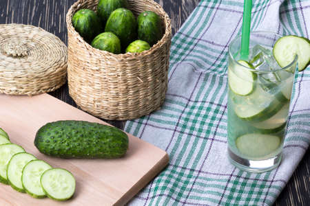 shooter drink: Summer cucumber cocktail and sliced cucumbers on wooden desk. Stock Photo