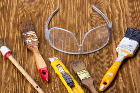putty knives: Construction tools: brushes, knife and glasses on wooden background Stock Photo