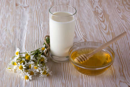 salubrious: Bowl with honey, glass with milk and chamomile flowers on the wooden table