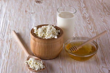 salubrious: Honey, cottage cheese and glass with milk on wooden background