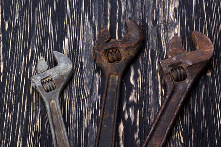housebuilding: Closeup adjustable wrenches on a wooden background