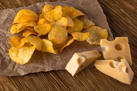 potatoe: Closeup of potatoe chips with cheese on wooden desk