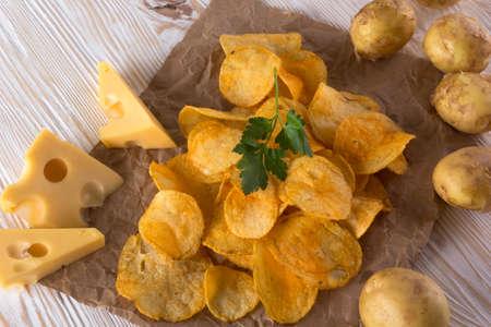 raw potato: Potato chips, raw potato and cheese on wooden background. Stock Photo
