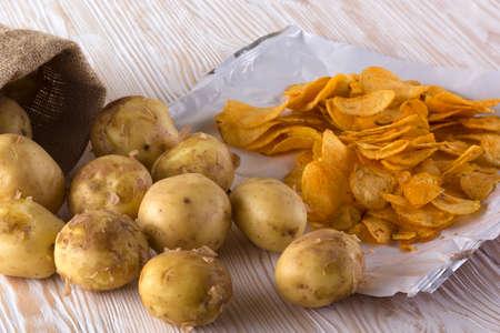 raw potato: Potato chips and raw potato on wooden background.