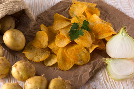 raw potato: Potato chips, raw potato and onion on wooden background.