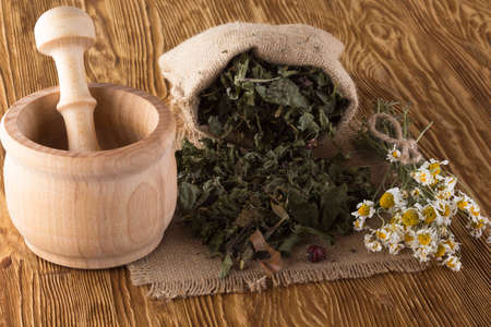 traditional healer: mortar and pestle with herbal tea on wooden background. Stock Photo