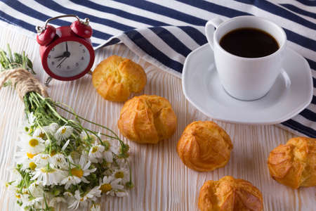 eclair: Eclair, coffee cup, alarm clock and charmomile on wooden background.