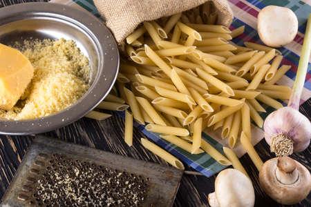 queso rallado: Ingredientes. Pasta, ajo, sal queso rallado y el champiñón en el fondo de madera.