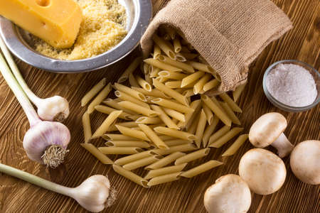 grated cheese: Ingredients. Pasta, garlic, grated cheese salt and champignon on wooden background.
