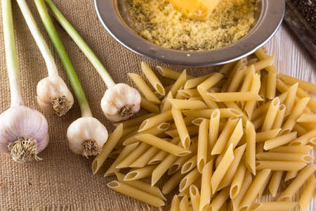 queso rallado: Pasta, grated cheese and garlic on wooden background