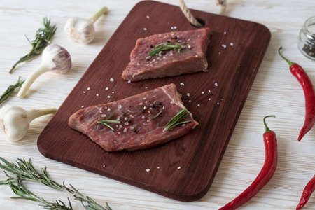 Fresh raw steaks with rosemary, pepper and garlic on wooden desk