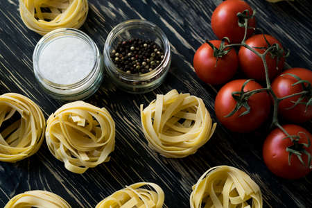 ingridients: Pasta ingridients and spice on wooden surface. Stock Photo