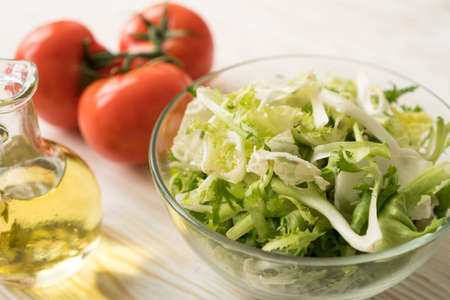 Healthy veggie salad ingridients. Tomato, lettuce and olive oil.