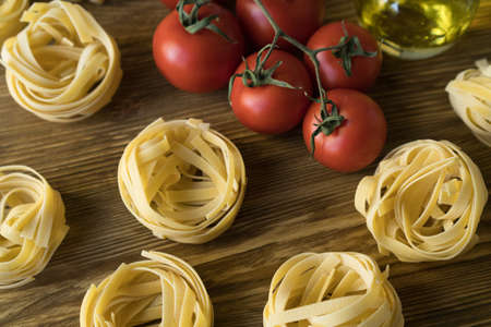 Pasta ingridients and spice on wooden surface. Imagens